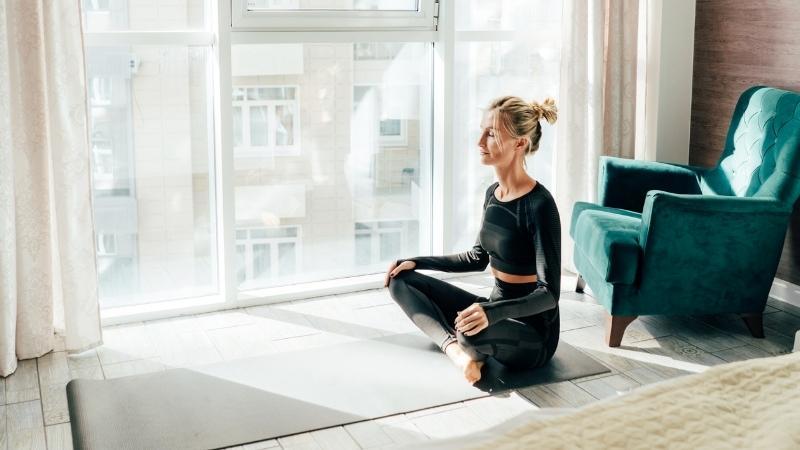 Eine Frau hat Motivation zum Meditieren und sitzt auf der Gymnastikmatte