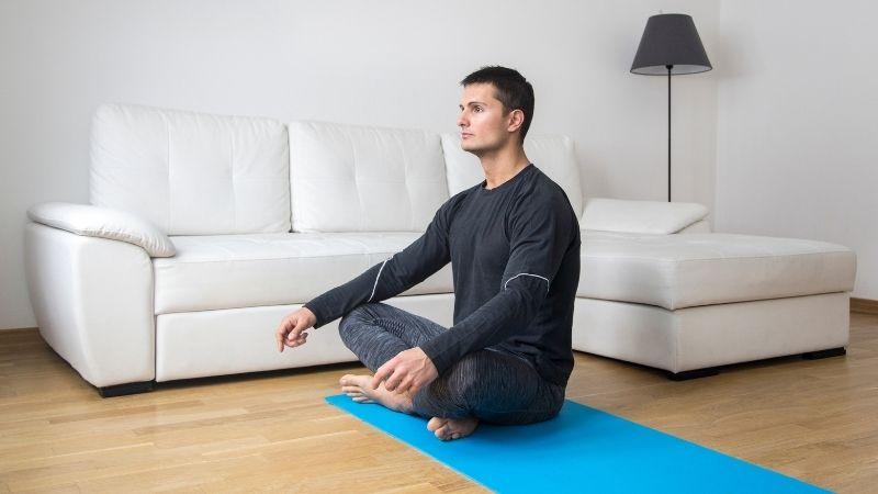 Ein Mann hat Motivation zum Meditieren und sitzt auf der Matte mit gekreuzten Beinen