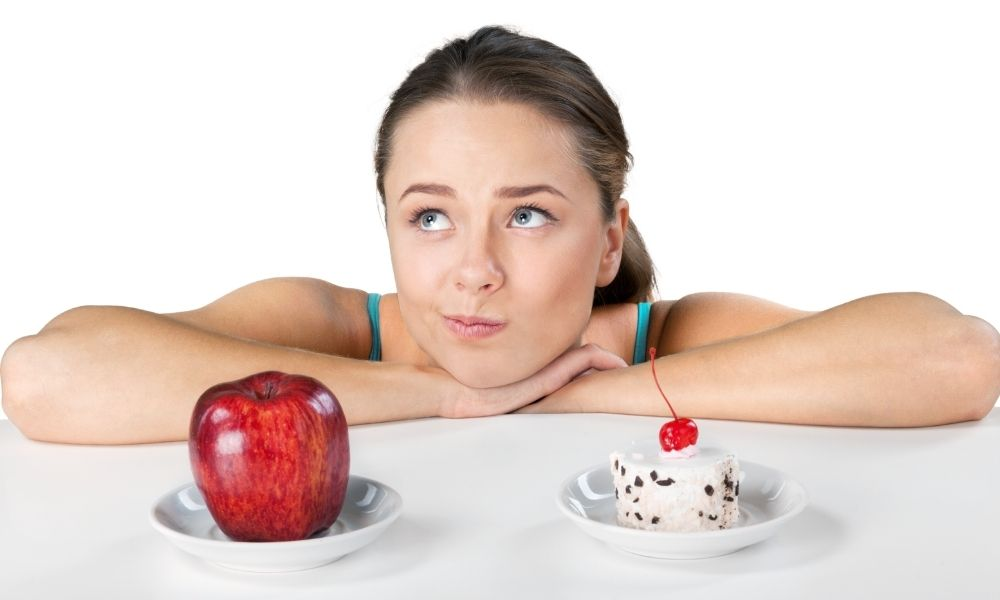 Veranschaulichung von diät-Problemen. Frau muss sich zwischen Kuchen und Apfel entscheiden.